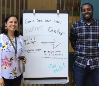 Wayne Hunter and Elisa Nevarez pose next to the Wellness Center board outside.