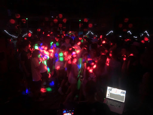 Students dance in the dark with colorful lights.