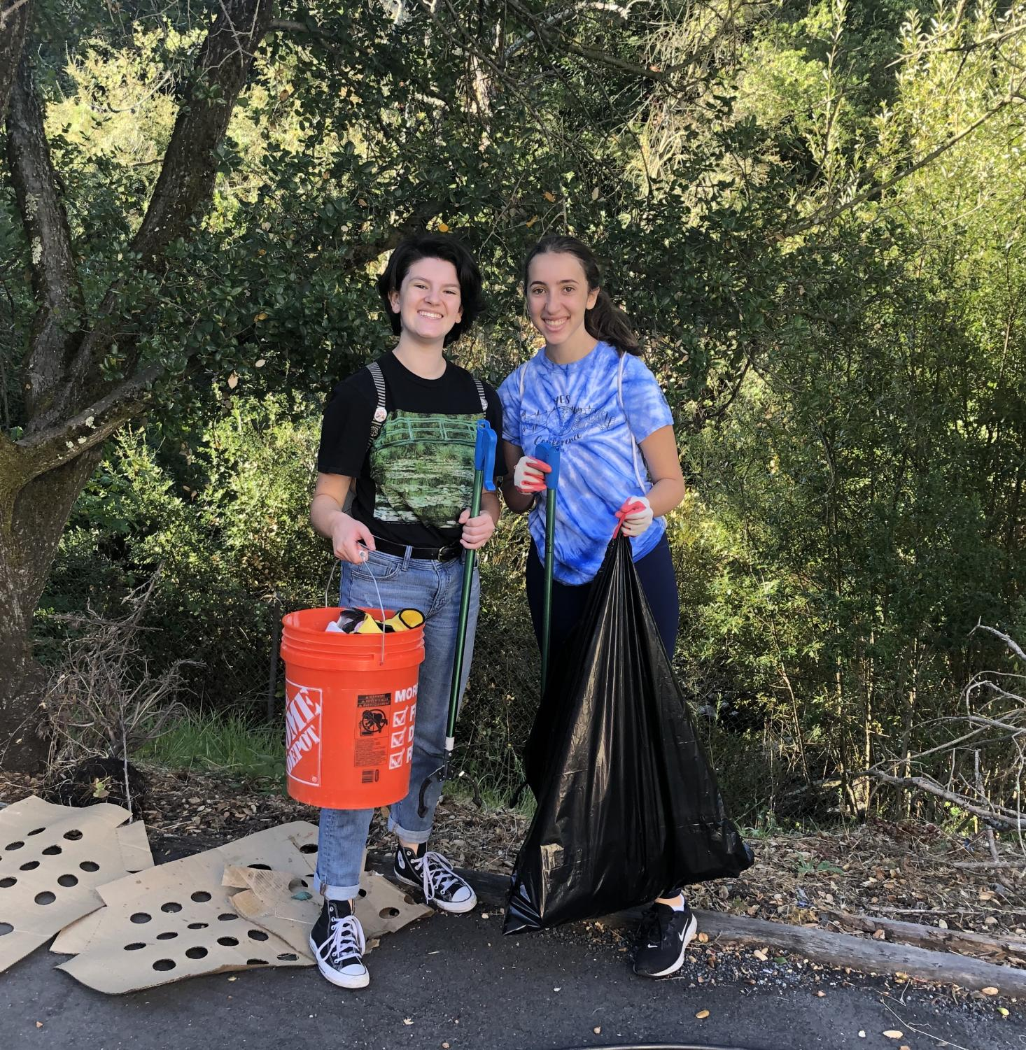 Sophomores Abby White (left) and Rebecca Libby (right) pose for a picture while helping to pick up trash.