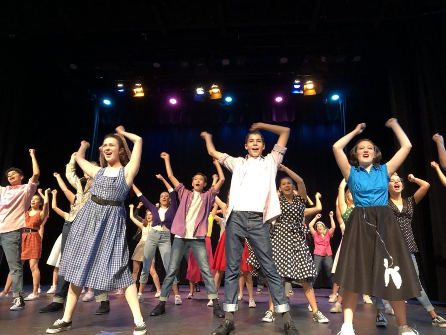 Musical Theater students enthusiastically dance on stage.